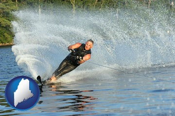 a young man waterskiing on a lake - with Maine icon