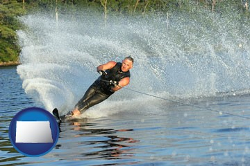 a young man waterskiing on a lake - with North Dakota icon