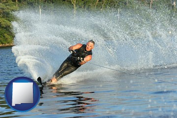 a young man waterskiing on a lake - with New Mexico icon