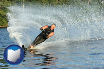 a young man waterskiing on a lake - with Ohio icon